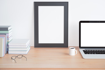 Blank wooden picture frame on wooden table with blank laptop scr