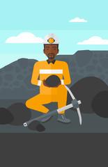 Miner holding coal in hands.