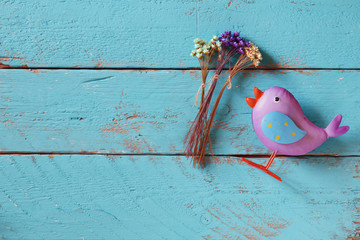 top view image of dried colorful flowers next to bird toy on old blue wooden background