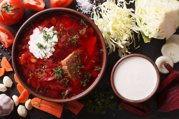 Ukrainian red soup borsch with ingredients on slate closeup. horizontal top view