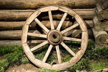 Old wooden coach wheel near barn