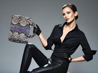 Beautiful woman in black  holds fashion handbag