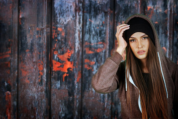 Teenager girl hipster on rusty fence background. Wearing hood.