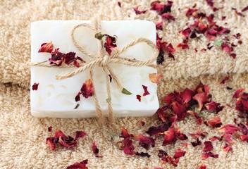Handmade bar of soap with herbal rose petals, beige terry bath towel.