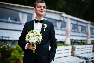 Portrait of elegant groom with wedding bouquet at hand