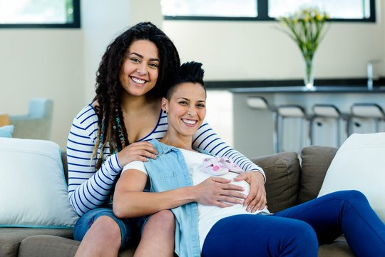 Pregnant lesbian couple with a pair of pink baby shoes