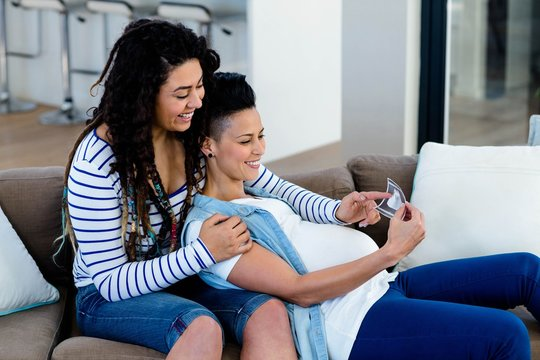 Pregnant lesbian couple looking at sonography report