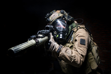 Soldier in gas mask aiming from his rifle.Selective focus/Man in uniform,helmet and gas mask aiming from assault rifle on  dark background
