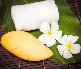 thai mango, towel  with plumeria flower on bamboo background