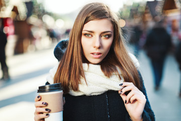 Cute girl with brown hair holding coffee on the street