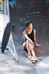 Attractive girl, sitting in the skatepark near her skateboard