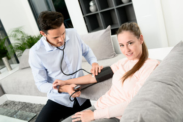handsome young doctor visiting a woman patient at home