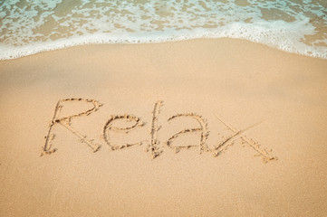 Relax message hand writing on the sand beach