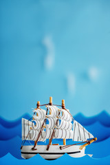 White Ship on blue wave with paper. Travel and adventure concept.