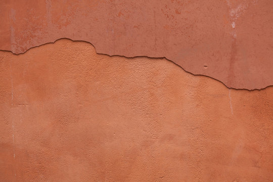 Old terracotta painted stucco wall with cracked plaster. Backgro