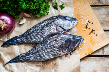 Fresh sea bass on board before preparation on rustic wooden back
