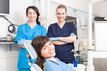 Portrait of smiling female dentist and assistant with female pat