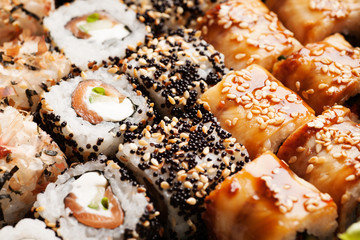 Sushi rolls with salmon, black caviar and seasame
