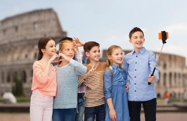 kids with smartphone selfie stick over coliseum