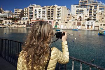 Woman  taking  photo of St. Julian's bay in Malta.