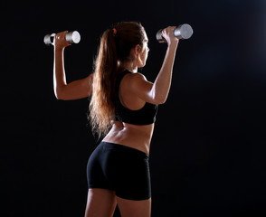 Young woman doing exercise with dumbbells, over black