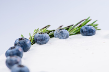 closeup decoration fresh blueberries and rosemary on cake with w