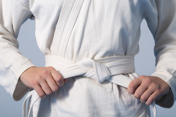 Photo sur Aluminium Combat Hands tightening white belt on a teenage dressed in kimono for martial arts