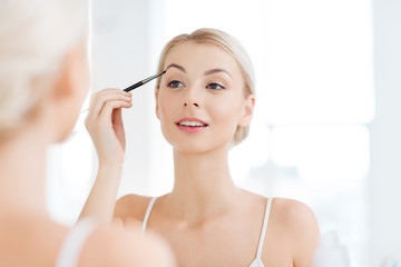 woman with brush doing eyebrow makeup at bathroom