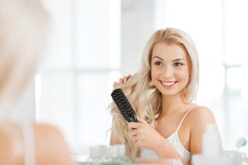 happy woman brushing hair with comb at bathroom