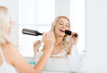 happy woman singing to hair brush at bathroom