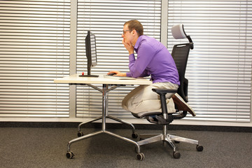 text neck - man in slouching position kneeling on ergonomic chair working with computer at desk