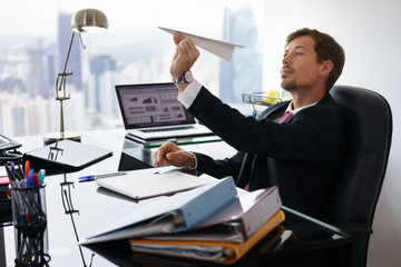 Bored White Collar Worker Throwing Paper Airplane In Office
