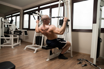 Young Man Doing Back Exercise on a Machine