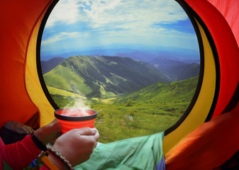 Woman lying in a tent with coffee ,view of mountains and sky