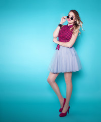 Full body portrait of young attractive blonde  woman wearing sunglasses skirt and high heels over a blue background