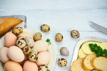 Quail eggs and hen egg with bread and butter on the white wooden table. Selective focus