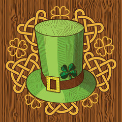Colorful St. Patricks Day hat with clover and ornament with Knots on wood background.