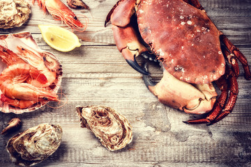 Steamed crab, shrimps and fresh oysters on wooden background