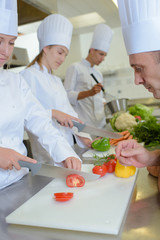 Chef watching students chop vegetables