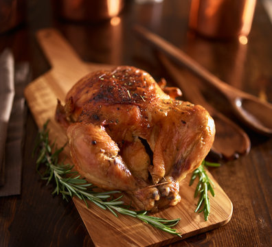 rotisserie chicken on wooden serving tray with herbs and rosemary