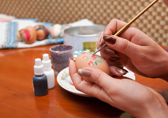 woman paints flowers on Easter eggs