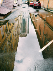 Beautiful houses reflected in a puddle