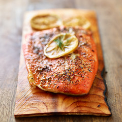 cooked salmon on top of cedar plank with herbs