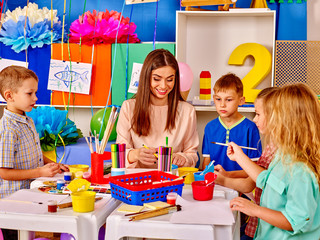 Kids with young teacher woman painting on paper at big table  together in  kindergarten .
