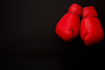 Two red boxing gloves in the upper corner of the frame over a black background, empty space