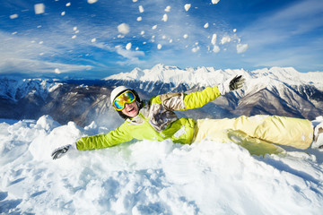 Happy woman in ski outfit throw snow up