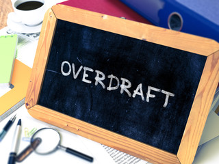 Overdraft - Chalkboard with Hand Drawn Text, Stack of Office Folders, Stationery, Reports on Blurred Background. Toned Image. 3D Render.