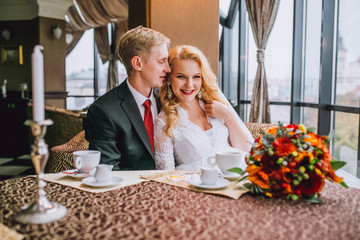 Happy bride and groom in vintage interior of restaurant