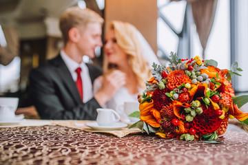 Happy bride and groom in vintage interior of restaurant