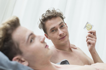 Germany, Saxony, Homosexual couple with condom, smiling